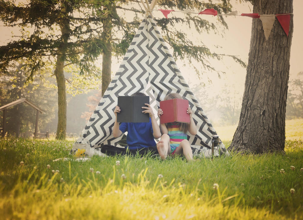 Two young children are reading books together outside in a teepee tent for a education or learning concept.