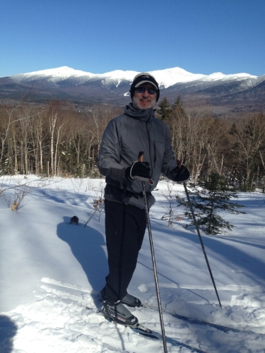 The 62 year old XCSkiResorts.com editor takes a break on the Mountain Road in the shadow of Mt. Washington