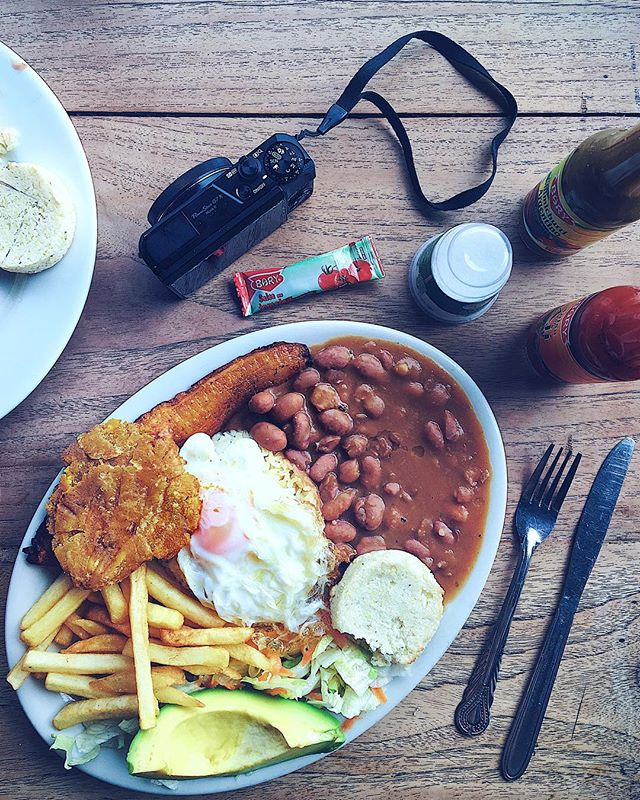 "🗣 What's the most caloric meal you've ever had?! 🍟🍔🍕 ——————— 🚨Ladies and gents- you're now staring 👀 at my answer haha! Let me introduce you to the ""healthy"" 💚 vegetarian version of Medellín's famous regional dish: the #BandejaPaisa. 🙀😜🙌🏼 ——————— The dish originates from a peasant farm worker 🇨🇴👨🏻‍🌾 tradition, where men would eat one MASSIVE, protein 🍗and carb-dense 🍞 meal a day, so that they'd have enough energy to work the fields till sun down. 💪🏼🌱👨🏻‍🌾 ——————— This vegetarian version 🌱💚 is a traditional bandeja paisa just without the meat. So normally they'd top this plate with sausage 🌭and beef (and the beans would be made with pork fat!) Remove the egg 🍳 and it's also be 100% vegan. 💯💚🌱 ——————— This meal gave me the strength ❤️💪🏼 to hike up Guatape, Colombia's 🇨🇴 famous #PiedraDePeñol- a massive landmark rock that randomly juts of the nearby landscape by around 700 feet feet. 😱🏞 ——————— I'd like to assume that my bandeja paisa gave me the strength to hike up its 750 stairs to read the top Of te cliffs! ❤️💪🏼🏞"