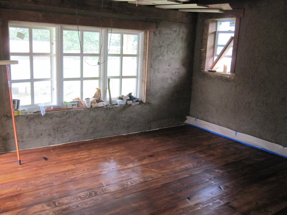 Light Straw Clay Walls with Rough Plaster & Stained Salvaged Floors