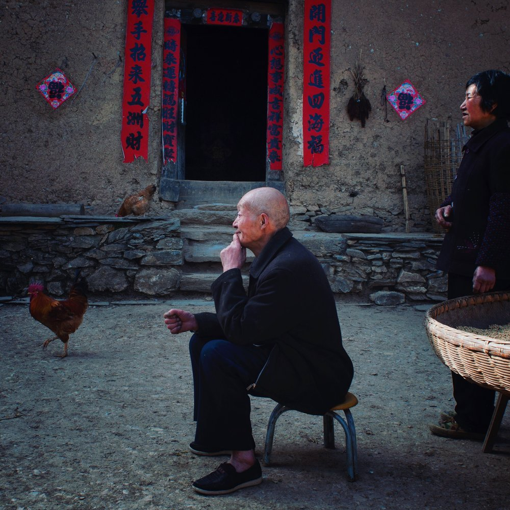 Two elderly farmers who are the last villagers left in a poor village on a mountain slope, Shaanxi Province. Photographed for China Pictorial