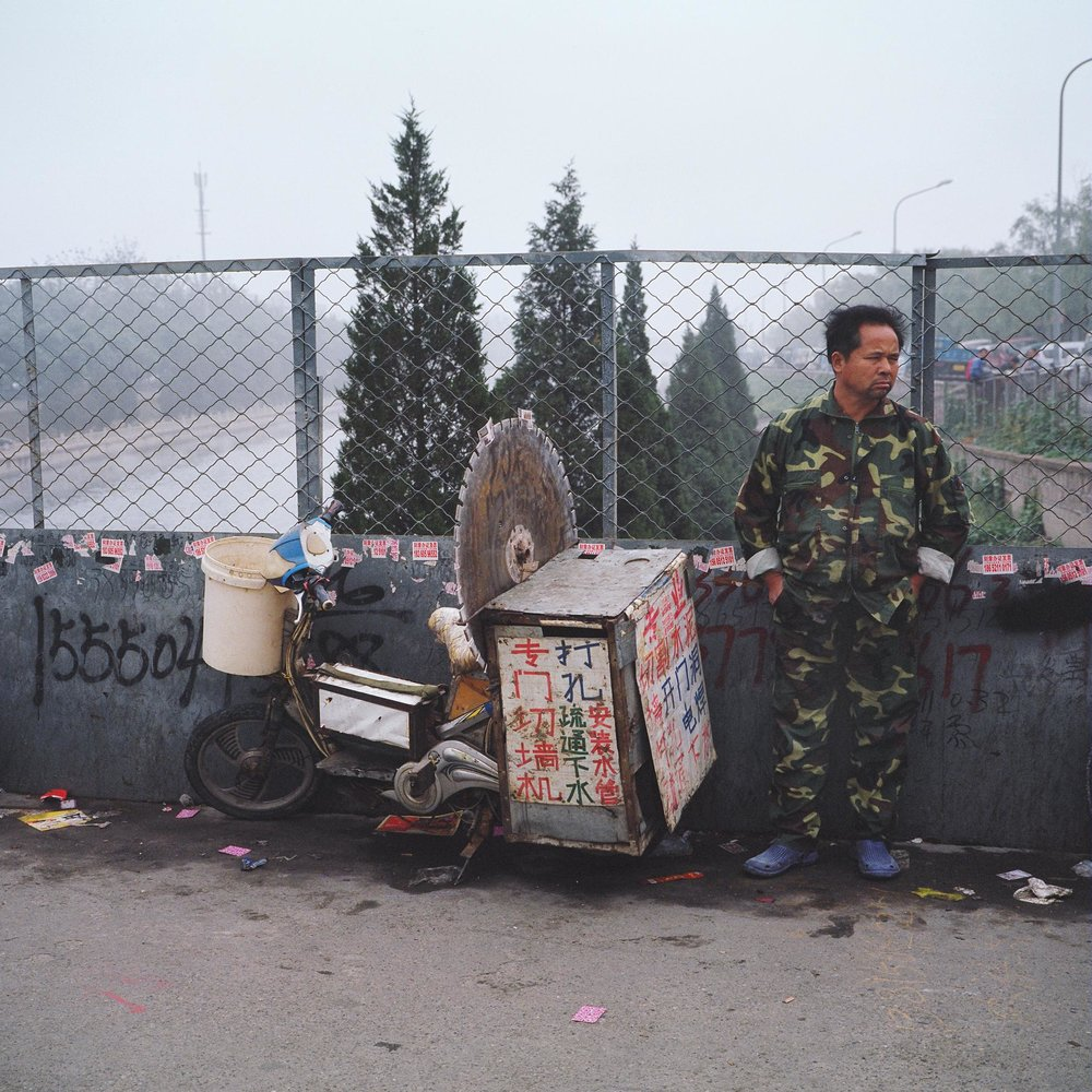 An unemployed man advertising his services on a bridge in Beijing. Photographed for Caixin