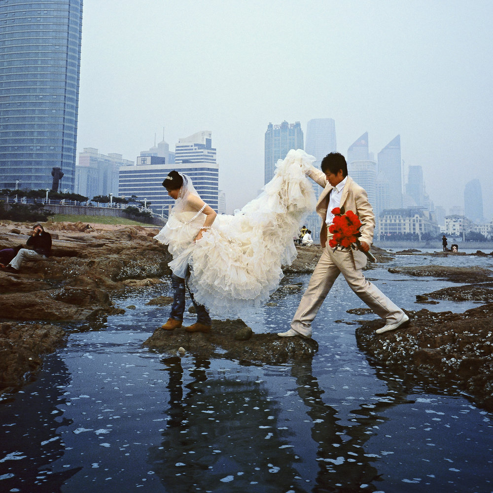A candid moment on a wedding shoot, as a couple gets swallowed by the tide. Qingdao.