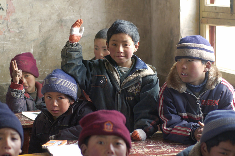 Tibetan children answer questions in a newly built school deep in the mountains of Qinghai Province. Photographed for Darzhong NGO