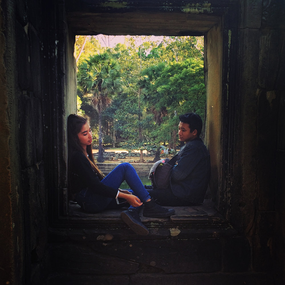 A young couple in an alcove of Angkor Wat temple complex. Siem Reap, Cambodia.
