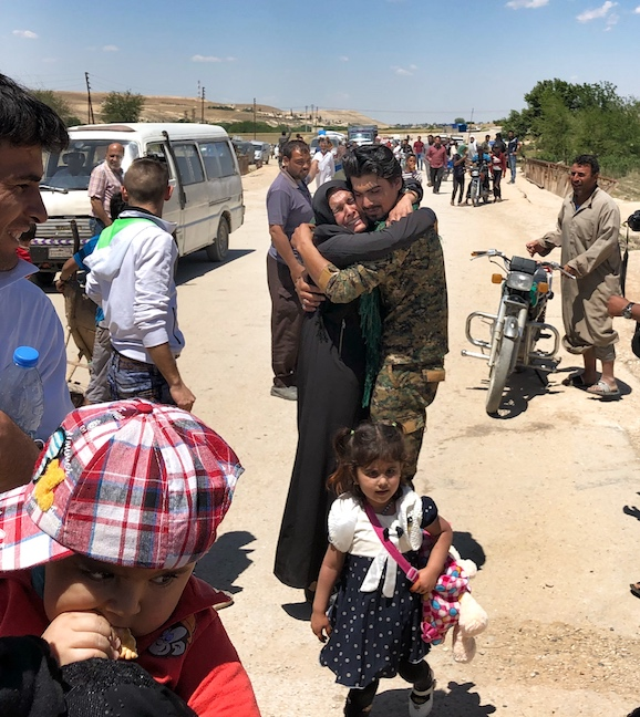 YPG soldier greets a family member who made it across the front line to safety