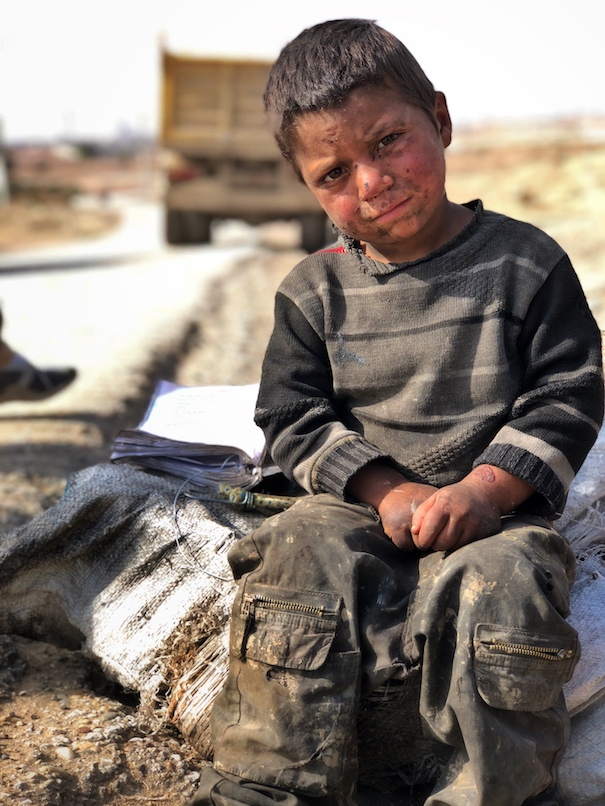Boy sells charcoal on the road