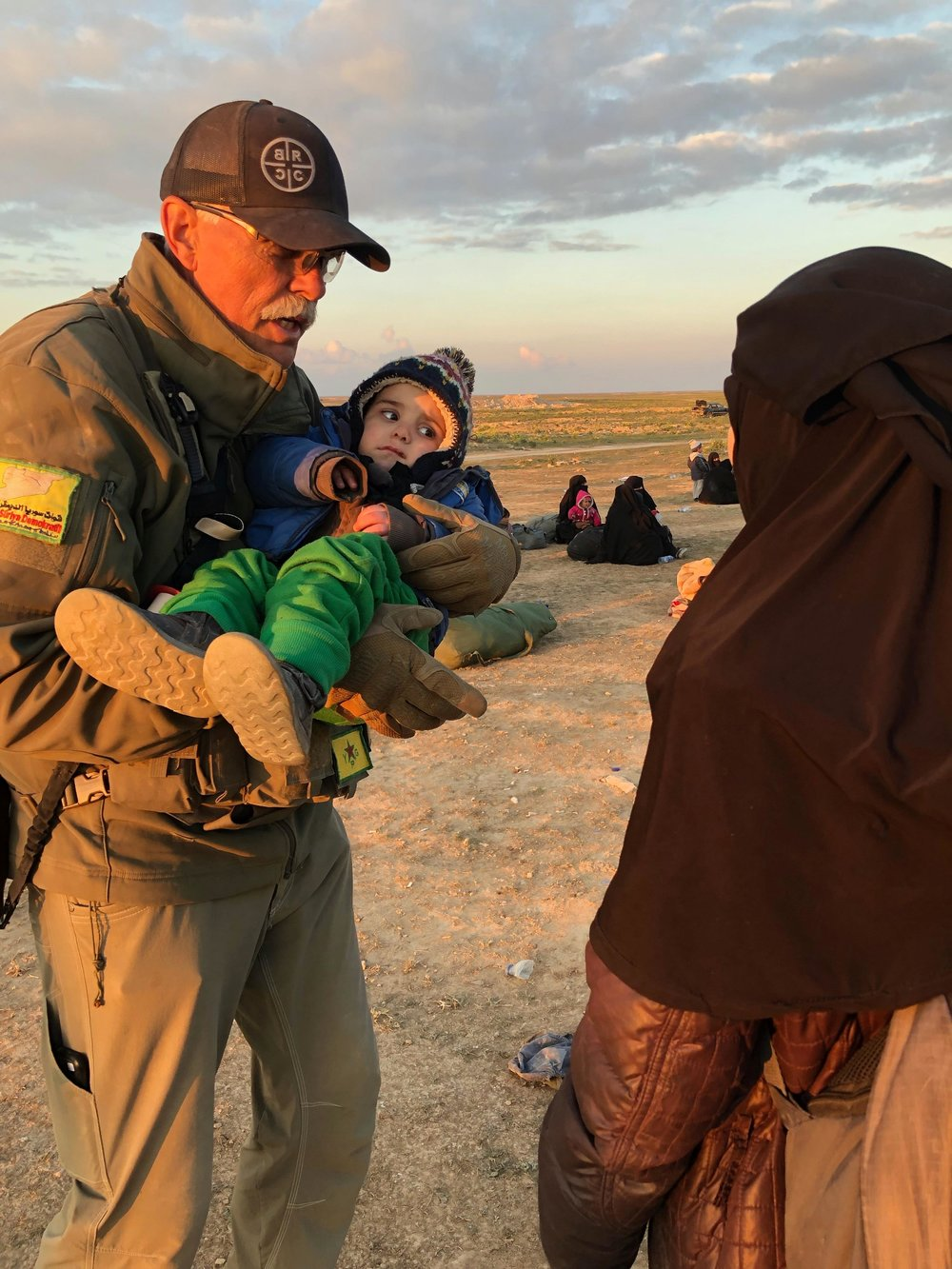 Paul Curtis Bradley carries a child near Baghuz