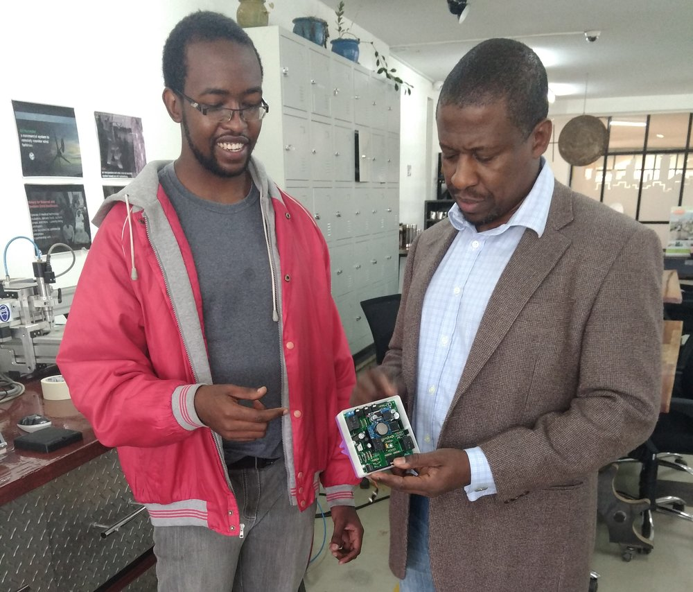 Dr. Kamau Gachigi, Gearbox Executive Director, admiring George Chege's product