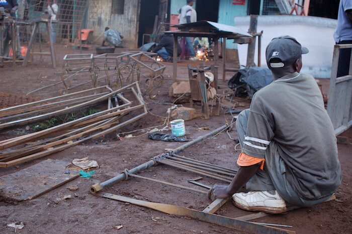 A man Jua Kali worker in Kenya uses a homemade welder. Courtesy Erik Hersman—CC by 2.0 license.