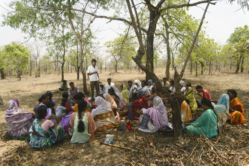 A gram panchayat meeting in progress. Villagers plan their day's action and roles in forest management including cleaning the area, patrolling, marking the trees and enlisting them in the panchayat records roster.