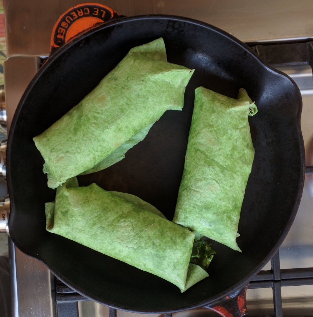 Placing the wraps into a skillet (or a sandwich press) seam side down to toast the tortilla and wilt the inner ingredients.