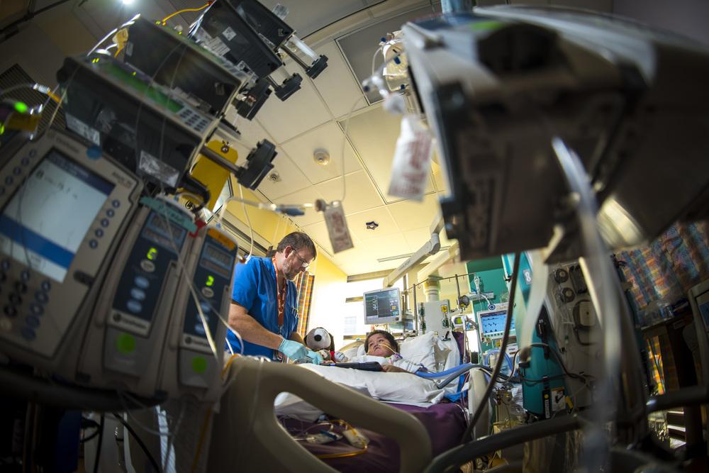 A nurse cares for a patient in the pediatric intensive care unit (PICU).