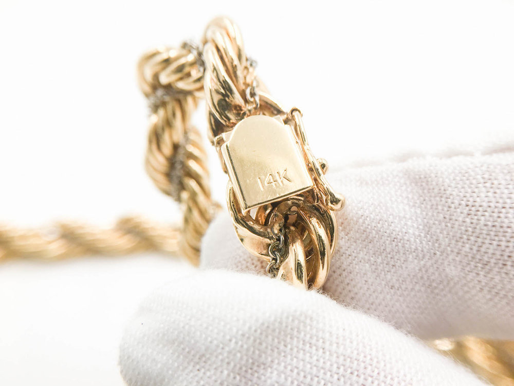14K stamp on a rope chain's clasp identifies it's pure gold percentage.