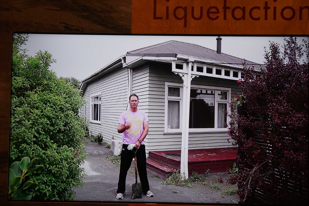A picture of a picture showing liquefaction in the suburbs.  All of the gray around the house is liquified soil that came up during and after the quake.  Although these houses did not fall down in the quake, over 1,000 had to be demolished and will never be rebuilt because the soil was too unstable.