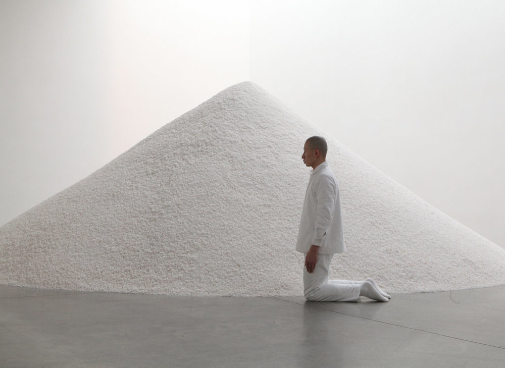 "Terence Koh circles a pile of salt on his knees in ""nothingtodo""NewYork 2011"