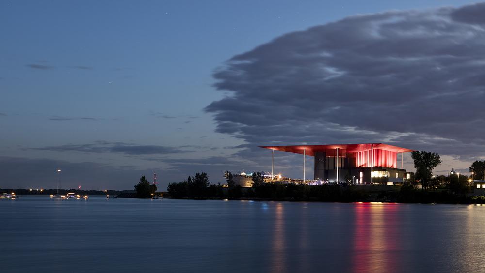 Vue de l'amphithéâtre la nuit à partir de l'Île Saint-Quentin. Les façades lumineuses sont réfléchies dans l'eau. Crédit photo © Adrien Williams