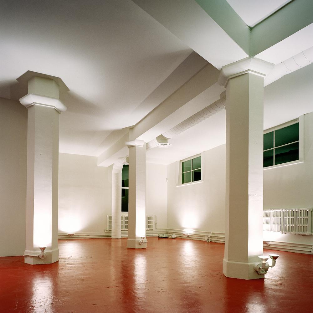 Le plancher de béton de la mezzanine est peint de couleur rouge pour dynamiser le fond de l'espace. Crédit photo © Marc Cramer.
