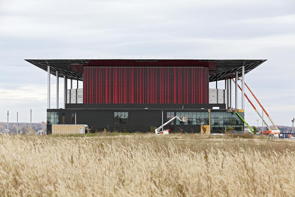 Photo de façade nord de l'amphithéâtre prise le 20 octobre 2014. Les panneaux de trois couleurs en alternance en cours d'installation. Crédit photo © Marc Gibert – adecom.ca