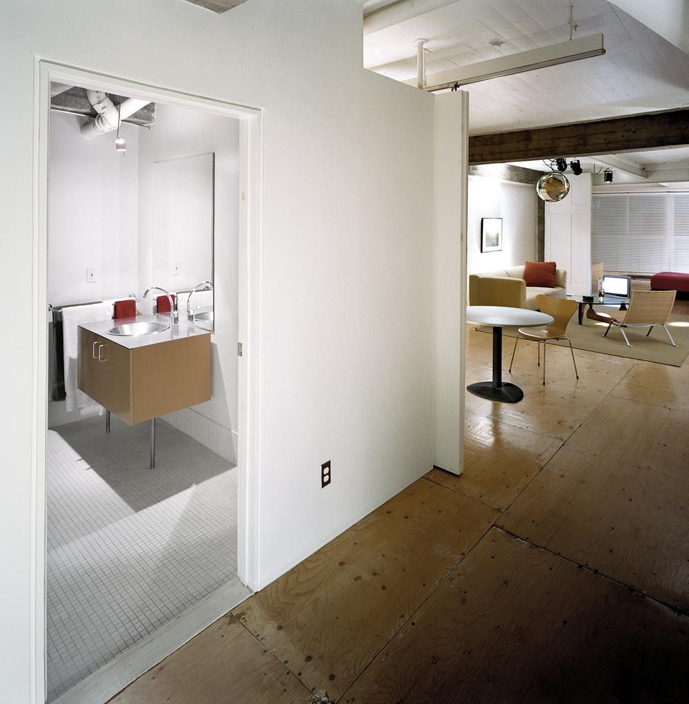 Vue vers l'espace central avec fenêtre au loin et la salle de bain sur le côté. Crédit photo © Marc Cramer
