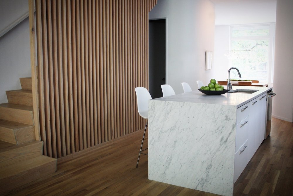All of the floors and wood details were finished to a matte blonde to create a fresh and bright feeling throughout.   The light wood plays nicely off the marble waterfall island.   Counter stools are Charles and Ray Eames for Herman Miller.