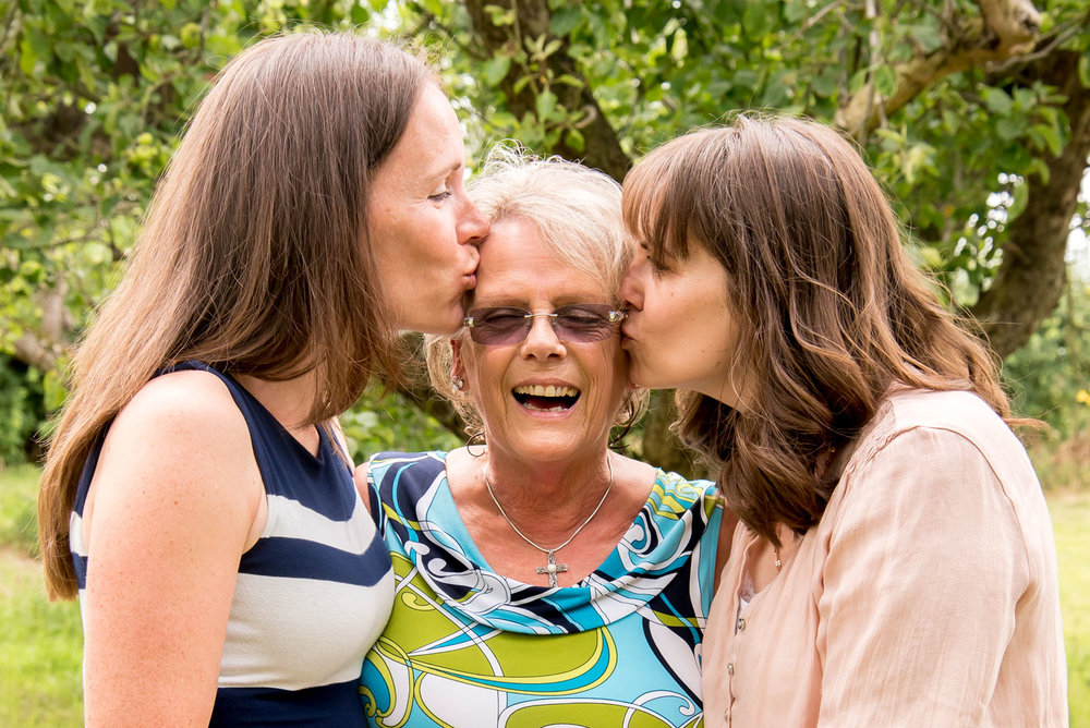 Family_photography_Ely_Cambridgeshire-3-women-daughters-kissing-mum-on-cheeks.jpg