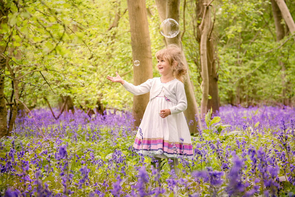 Baby_photography_Ely_Cambridgeshire-little-girl-playing-with-bubbles-in-bluebell-wood.jpg
