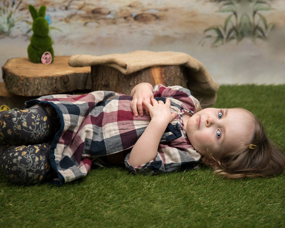 baby_photography_Ely_Cambridgeshire_easter_mini_session_pooh_themed_backdrop_little_girl_lying_on_the_grass.jpg