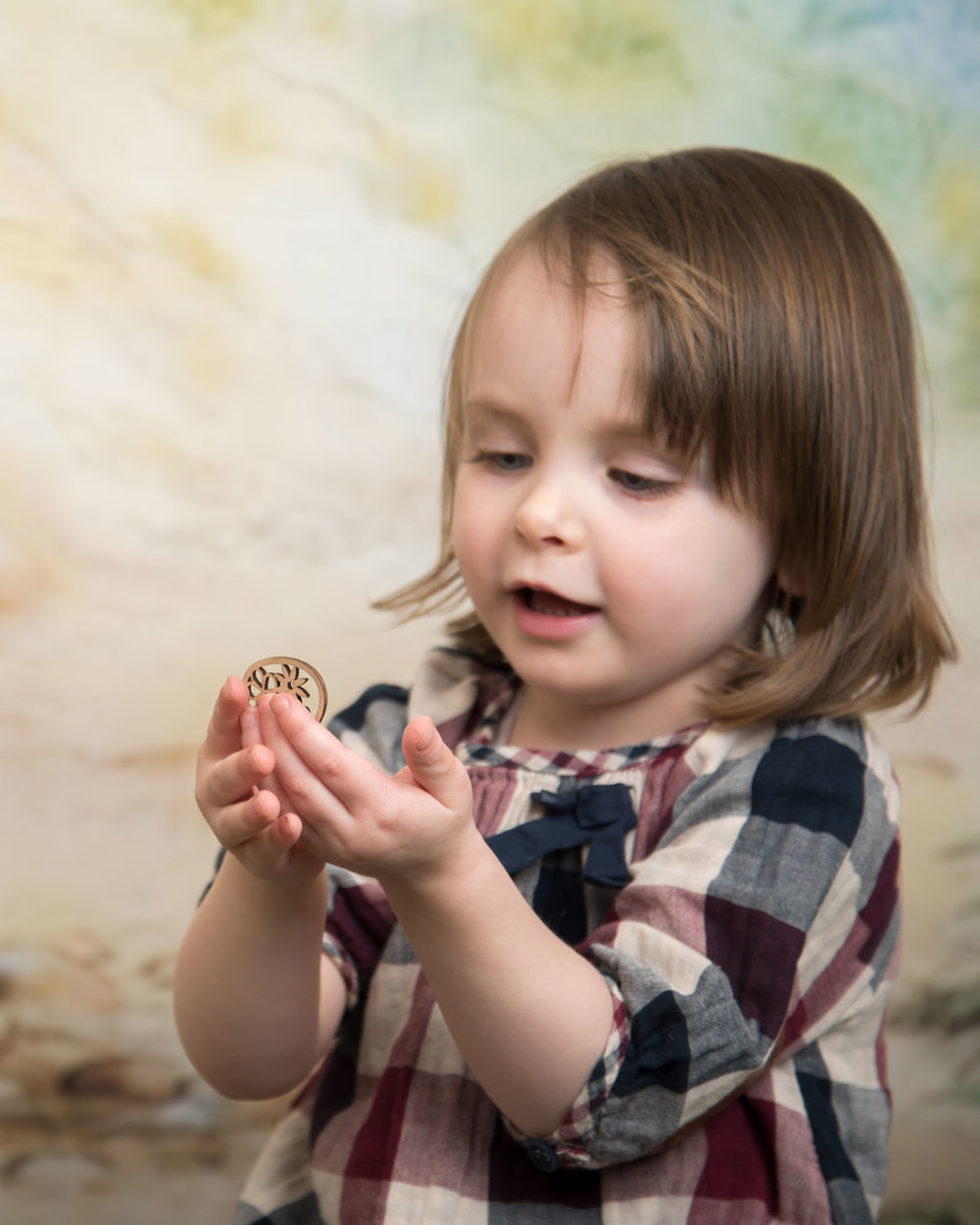 baby_photography_Ely_Cambridgeshire_easter_mini_session_pooh_themed_backdrop_girl_playing_with_egg.jpg