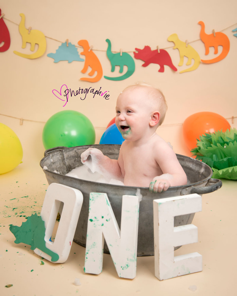 Cake_smash_photography_Ely_Cambridgeshire_first_birthday_dinosaur_themed_boy_in_tin_bath_looking_away_from_camera.jpg