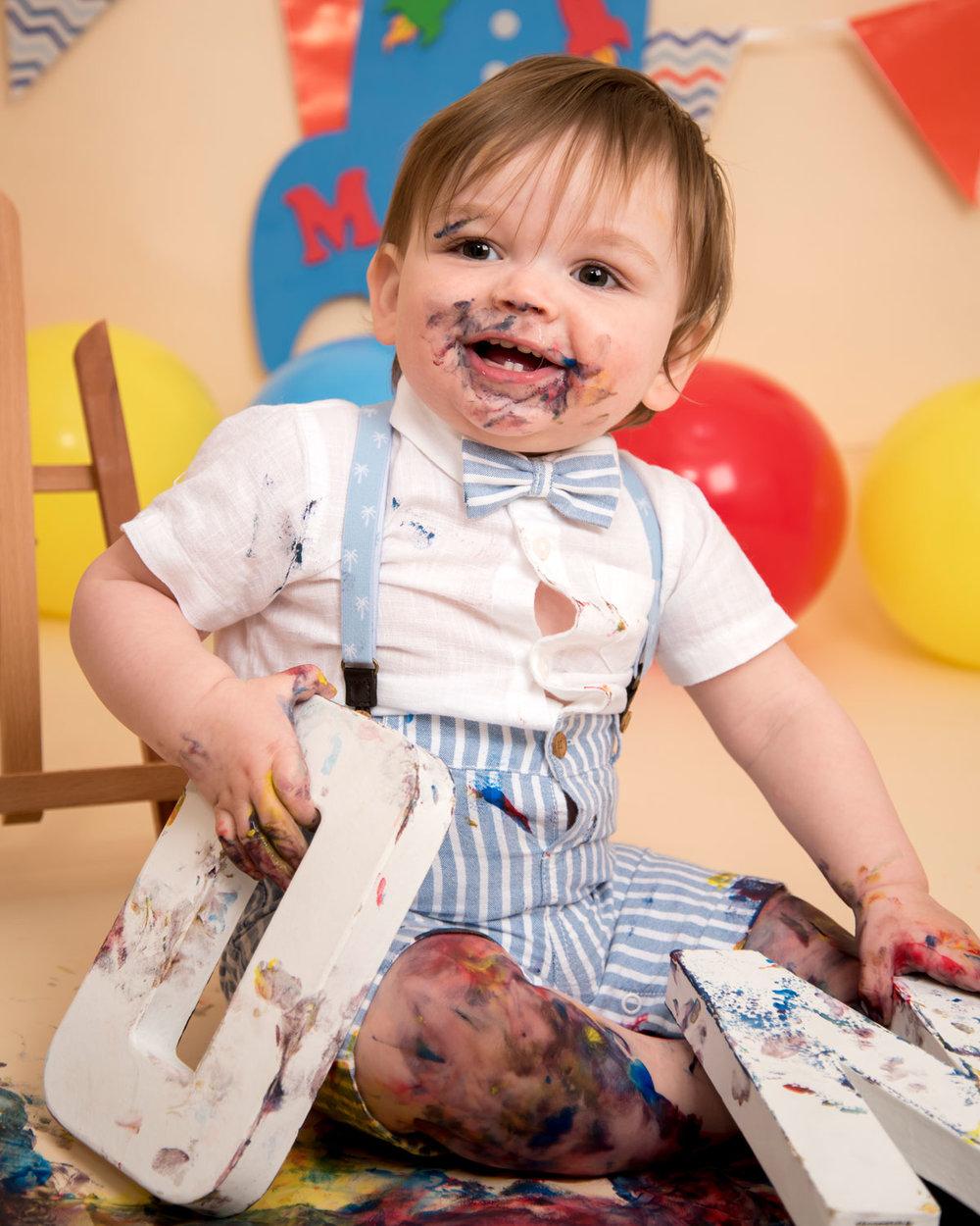 Baby_cake_smash_photography_Ely_Cambridgeshire_paint_splash_cake_smash_alternative_messy_play_first_birthday_for_milo (6).jpg