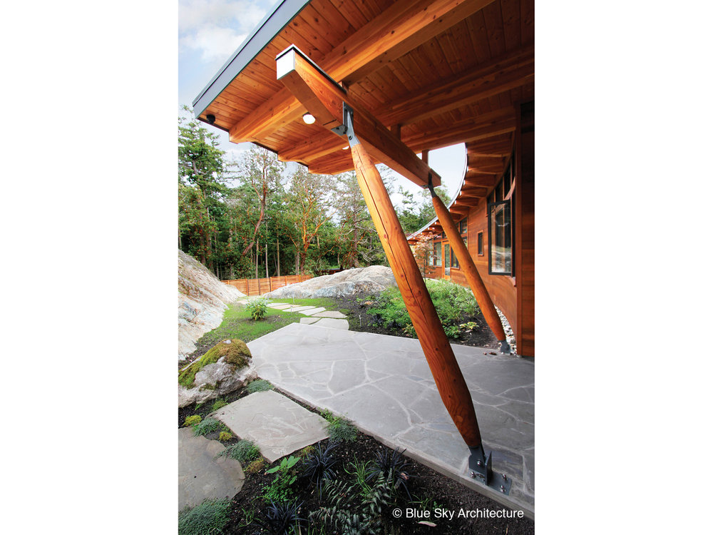 Heavy timber columns and beam on entryway of off-grid home