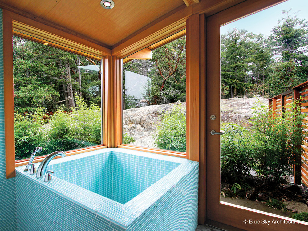 Solar crest bathroom with tiled Japanese soaker tub and forest view