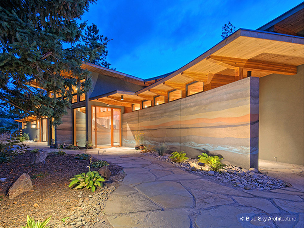 Rammed earth and heavy timber entryway on custom home design