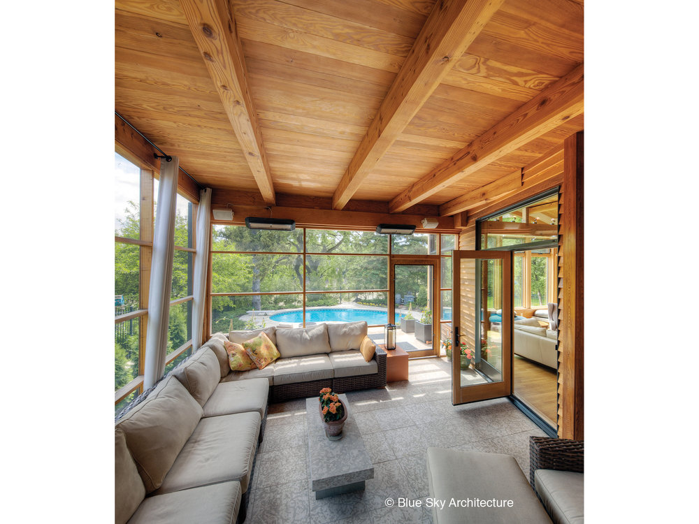 A screened-in porch with wood-framed ceiling
