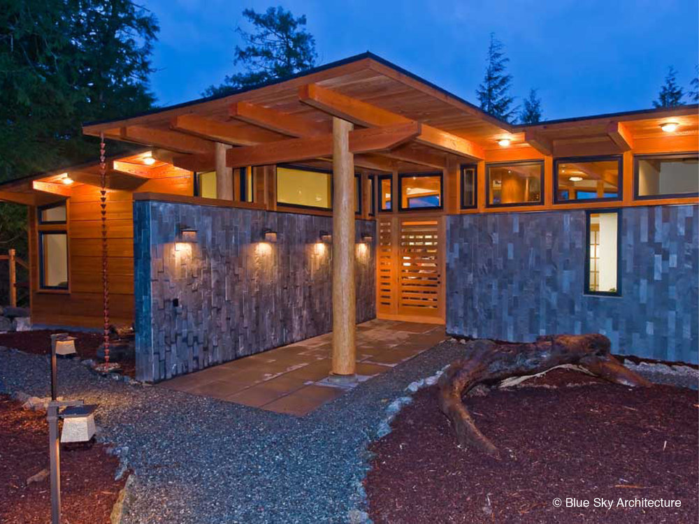 Stone and wood entry with custom door at the Ucluelet House entrance