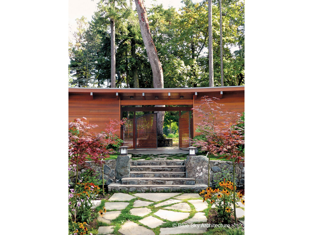 Wood gate and stone steps in the garden courtyard of Booklovers House