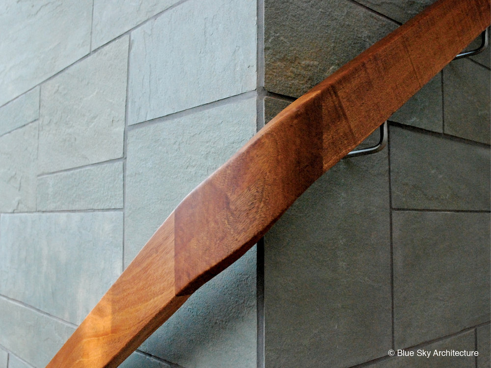 Wood handrail wraps around the slate walls of Ridge House