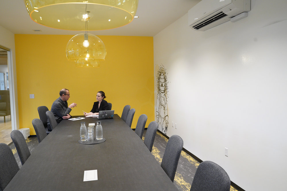 """The Hive - The ultimate spot for board meetings, training sessions and workshops. The Hive is guaranteed to impress with a full-length, floor-to-ceiling white board wall, 65"""" fully adjustable Apple TV for easy presenting, in-table power, and a webcam. Seats up to 16 table-sideMembers: $40/hour after free credits are usedNon-members: $45/hour M-F 8am - 5pm; $55/hour after 5pm, or on weekends"""