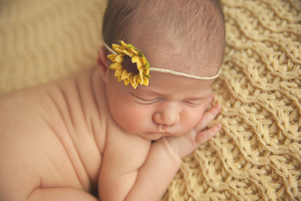 girl newborn with wrinkles on yellow with sunflowers