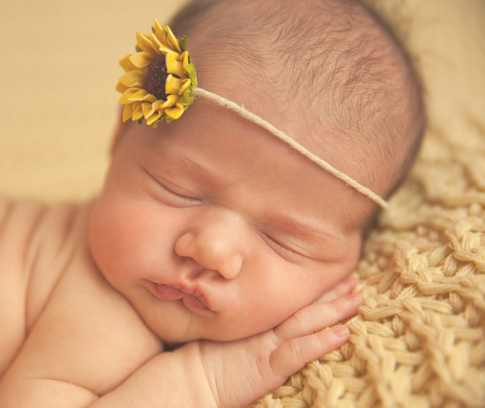 newborn girl on yellow with sunflower closeup on face