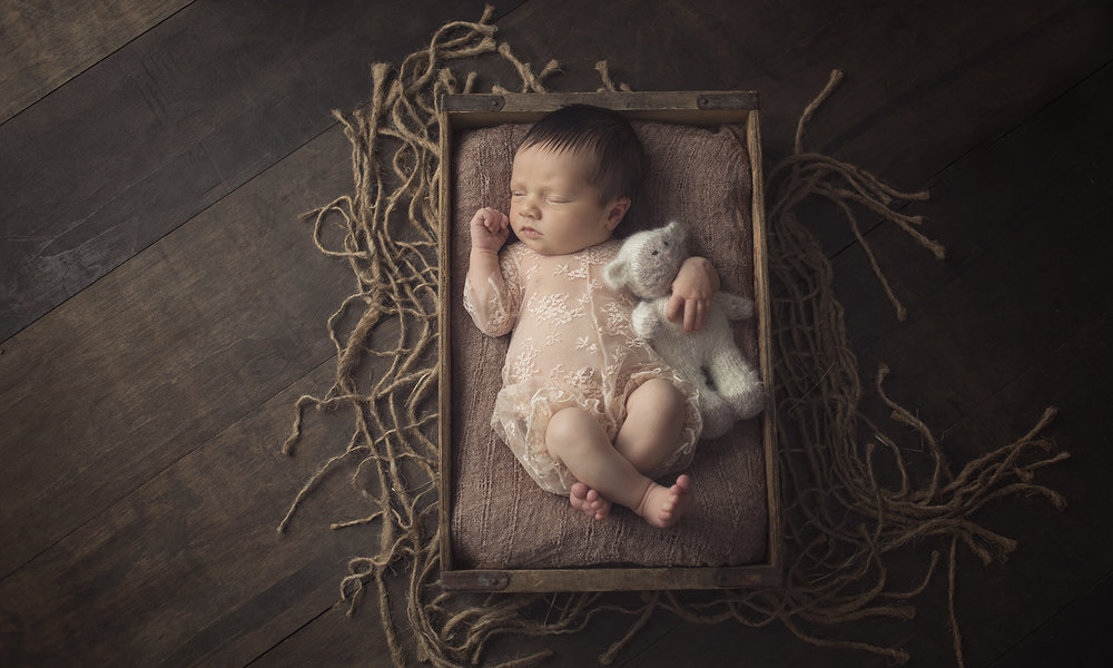 dark hair beauty posed in vintage wood crate with lace romper and knitted lamb lovie on wood floor and burlap underlay at newborn studio in dallas texas