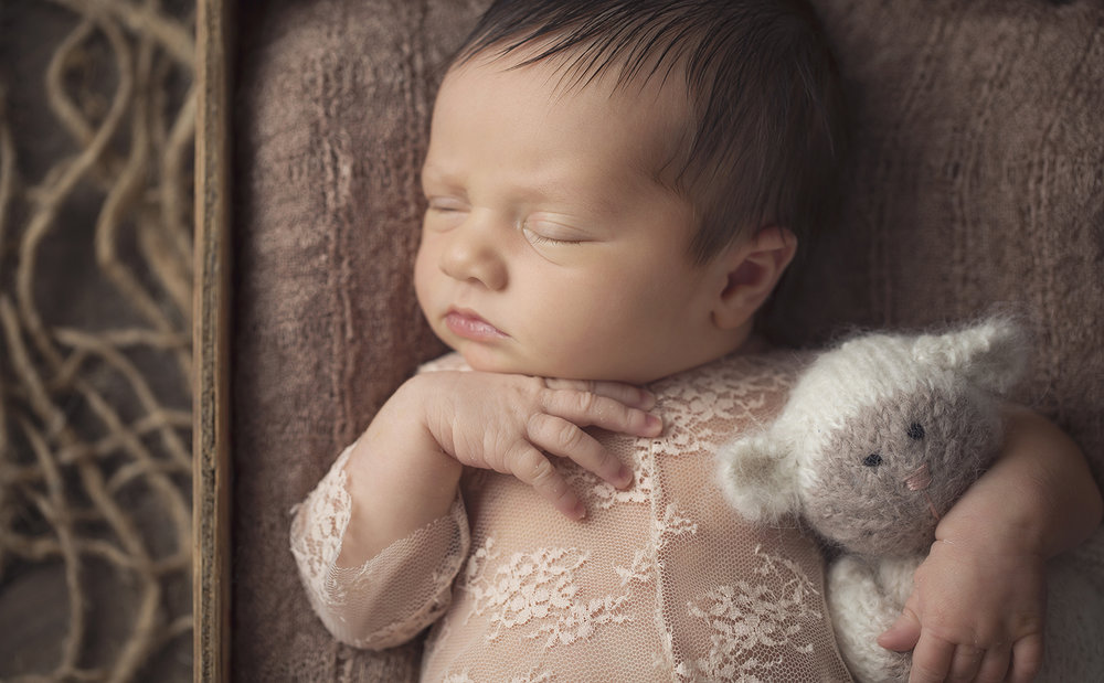 sleeping newborn girl in lace romper posed with knitted lamb lovie in vintage wood crate with burlap underlay on wood floor at the newborn studio in dallas texas