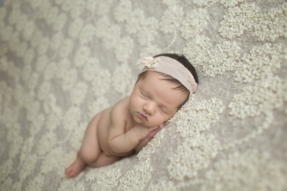 creme backdrop with dark hair newborn baby girl posed with hands under chin and facing forward with peach headband with dainty bow and baby's breath at the newborn studio in dallas texas