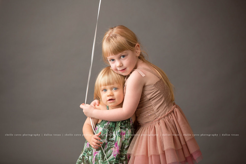big sister hugging little sister. both blonde little girls with big blue eyes on a dark gray backdrop holding a big round pink balloon