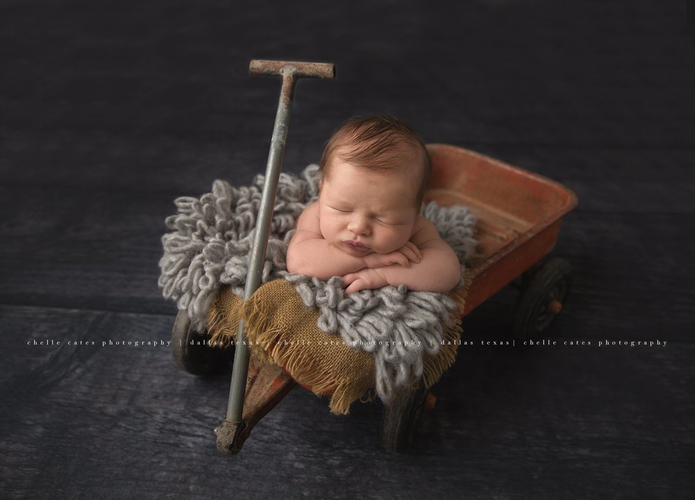 Handsome 7 day old baby boy photographed in a vintage red wagon with a burlap and gray looped bump blanket. Gray floor under him and the wagon. Newborn is posed with his face forward facing and his hands placed on top of each other. Baby boy is photographed at chelle cates photography in dallas texas.