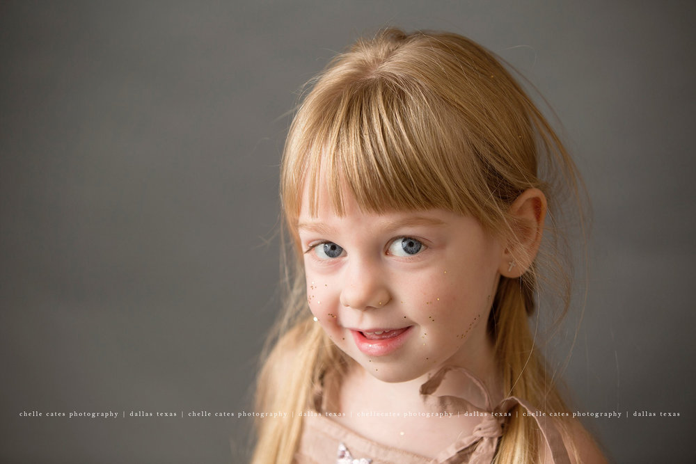 Professional portrait of 4 year old blonde cutie. She is wearing a pink tutu du monde dress from Australia. Her hair is braided on both side. She has gold glitter on her cheeks. This portrait was taken at chelle cates photography in Dallas Texas for her 4 year old birthday.
