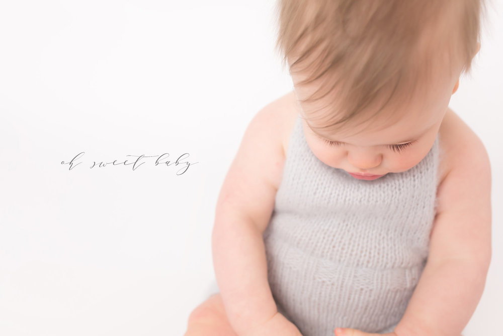 6 month little boy siting in a knitted pale blue romper. He has very long eye lashes and he is looking down at his hands. the little boy has perfect little part in his light brown hair as he sits on the white background.