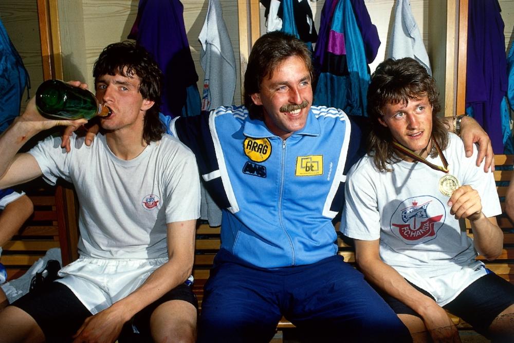 Sagde du tysk fodboldhår? Hansa Rostocks træner Uwe Reinders sidder omgivet af Jens Wahl og Henri Fuchs efter pokaltriumfen i 1990/1991-sæsonen.   Foto:Getty Images