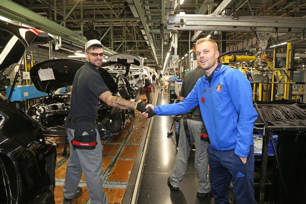 Få dage efter den britiske regering lavede en aftale med Nissan-ledelsen, var spillerne fra Sunderland på besøg på fabrikken, der er byens største arbejdsplads. Her hilser Sebastian Larsson på en af de ansatte. Foto: Getty Images